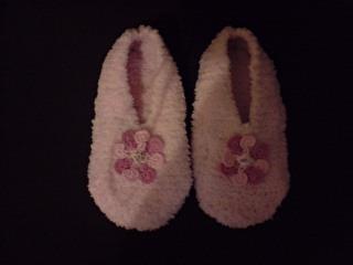 Chaussons rose en laine avec fleurs brodées.