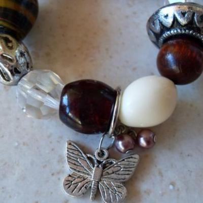 Bracelet marron, perles, papillon et pampilles.