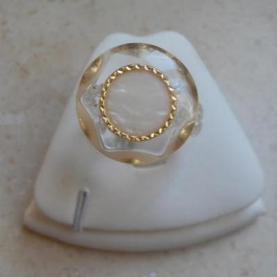 Bague ronde blanche et dorée.
