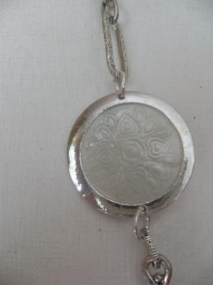 Sautoir métal et ronds émail blanc.