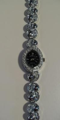 Montre ovale noire-métal et strass.