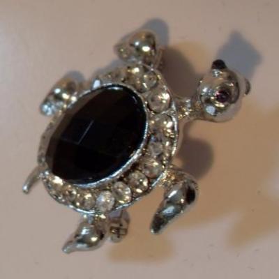 Broche tortue argentée et strass noir.
