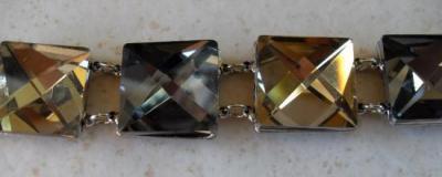 Bracelet large et carrés de strass.