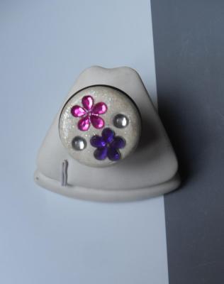 Bague ronde, gros cabochon blanc pailleté et fleurs strass rose-violet.