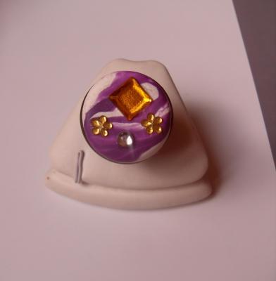 Bague ronde, gros cabochon blanc-violet, carré orange et fleurs strass.
