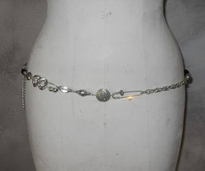 Ceinture-bijou, chaîne-maillons, grosse perle noire, épingles et strass.