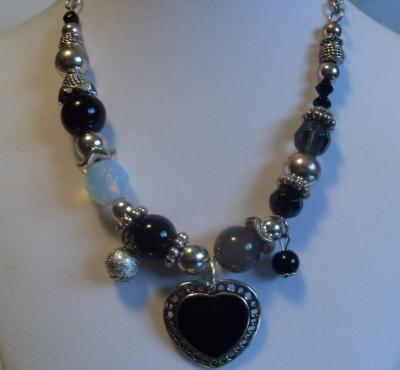 Collier perles et métal argenté, gros coeur noir et pampilles.