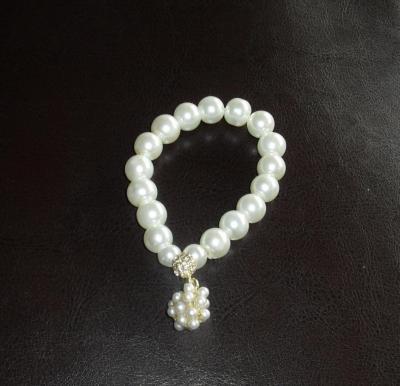 Bracelet blanc, perles de culture, strass blanc et breloque.