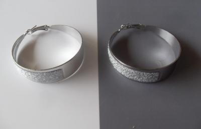 Boucles d'oreilles large anneau, effet pailleté et métal argenté.